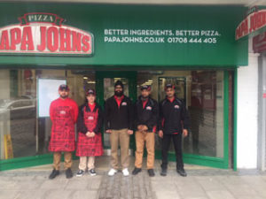 Papa John's franchisees Parry Singh and Tony Kalsi outside their new site in Elm park, east London, with staff