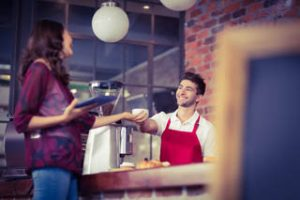 A waiter serves a customer in a coffee shop
