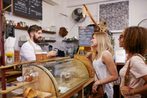 Waiter taking coffee order from two young female customers standing at cafe counter
